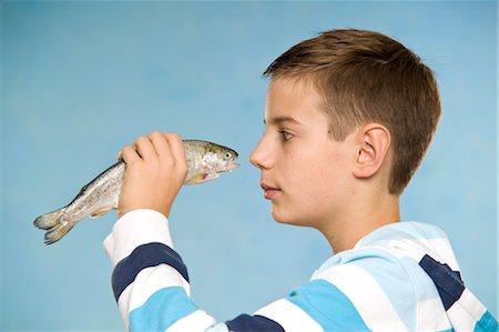 Boy Holding Raw Fish Stock Photo - Premium Royalty-Free, Code: 600-03456220