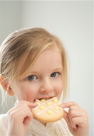 Little Girl Eating an Easter Cookie Stock Photo - Premium Royalty-Free, Code: 600-03456686