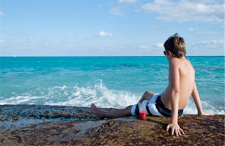 Boy Sitting by Surf, Playa del Carmen, Yucatan Peninsula, Mexico Stock Photo - Premium Royalty-Free, Code: 600-03456883
