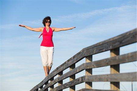 Woman Balancing on Wooden Railing, Honeymoon Island State Park, Florida, USA Stock Photo - Premium Royalty-Free, Code: 600-03484699