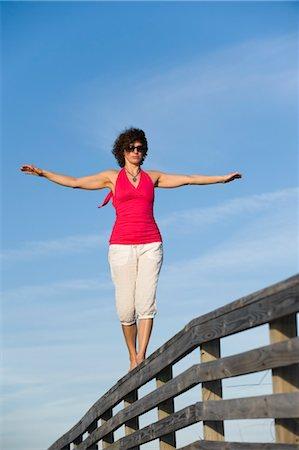 Woman Balancing on Wooden Railing, Honeymoon Island State Park, Florida,USA Stock Photo - Premium Royalty-Free, Code: 600-03484700