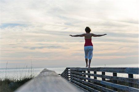 Woman Balancing on Wooden Railing, Honeymoon Island State Park, Florida, USA Stock Photo - Premium Royalty-Free, Code: 600-03484701