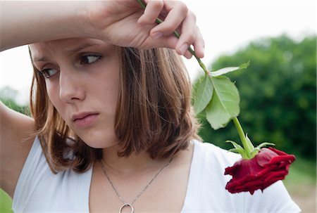 sad lovers break up - Teenage Girl Holding a Red Rose Stock Photo - Premium Royalty-Free, Code: 600-03490326
