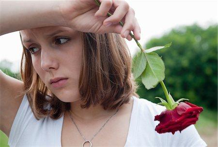 sad lovers break up - Teenage Girl Holding a Red Rose Stock Photo - Premium Royalty-Free, Code: 600-03490326