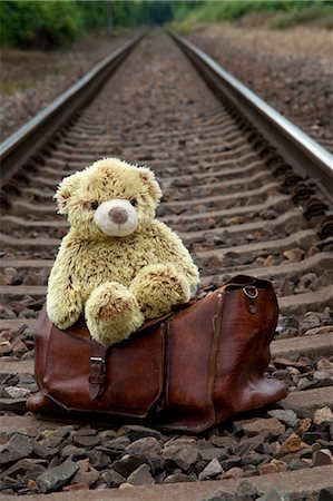 Teddy Bear and Suitcase on Train Tracks Stock Photo - Premium Royalty-Free, Code: 600-03490332