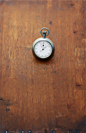Close-up of Stopwatch on Wooden Surface Stock Photo - Premium Royalty-Free, Code: 600-03553428
