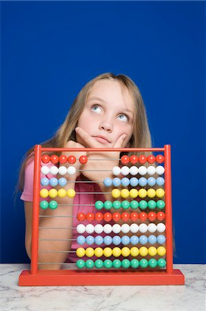 Young Girl Counting With Abacus Stock Photo - Premium Royalty-Free, Code: 600-03615843