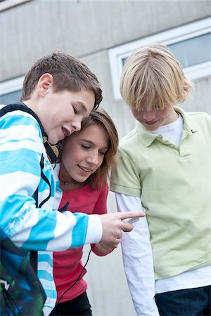 Teenagers Looking at MP3 Player, Mannheim, Baden-Wurttemberg, Germany Stock Photo - Premium Royalty-Free, Code: 600-03738180