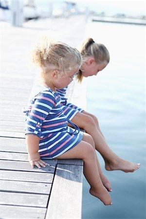 Girls Sitting on edge of Dock Stock Photo - Premium Royalty-Free, Code: 600-03738704