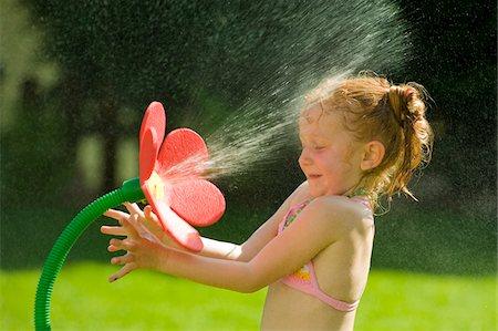 Girl Playing with Flower Sprinkler, Salzburg, Austria Stock Photo - Premium Royalty-Free, Code: 600-03768640
