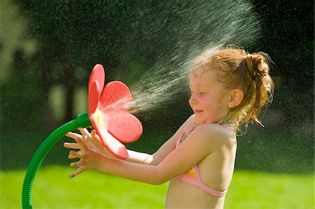 Girl Playing with Flower Sprinkler, Salzburg, Austria Stock Photo - Premium Royalty-Free, Code: 600-03768640