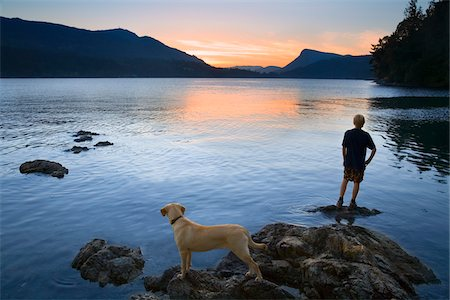Teenager and Dog looking at Sunset, Fulford Harbour, Salt Spring Island, British Columbia, Canada Stock Photo - Premium Royalty-Free, Code: 600-03814746