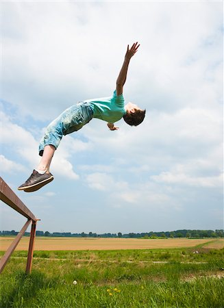 Boy Jumping off Trampoline Stock Photo - Premium Royalty-Free, Code: 600-03836155