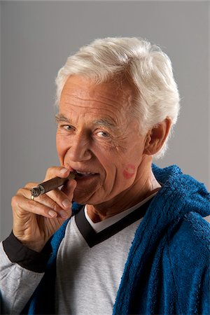 Man Smoking Cigar with Lipstick Kiss on Cheek Stock Photo - Premium Royalty-Free, Code: 600-03865084