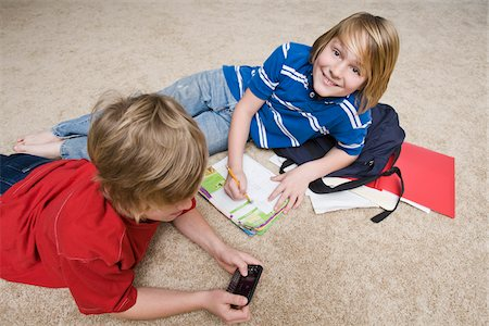 Boys Doing School Work and Using Cellular Telephone, Tallahassee, Florida, USA Stock Photo - Premium Royalty-Free, Code: 600-03865583