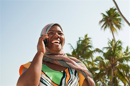 Woman Using Cell Phone, Nyota Beach, Unguja, Zanzibar, Tanzania Stock Photo - Premium Royalty-Free, Code: 600-03907373