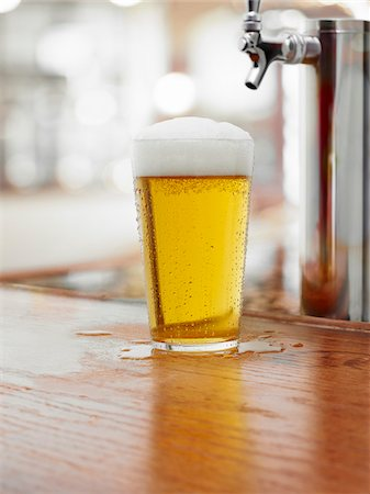 Glass of Beer on Bar Counter Stock Photo - Premium Royalty-Free, Code: 600-03907693