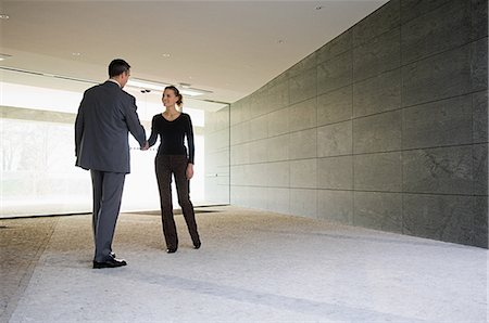 Businesspeople shaking hands in empty office Stock Photo - Premium Royalty-Free, Code: 614-05399601