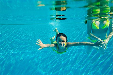 Woman with girl swimming in swimming pool, underwater view Stock Photo - Premium Royalty-Free, Code: 614-05399613