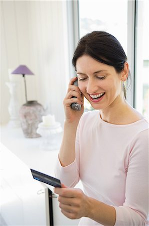 person on phone with credit card - Woman home shopping on phone with credit card Stock Photo - Premium Royalty-Free, Code: 614-05399665