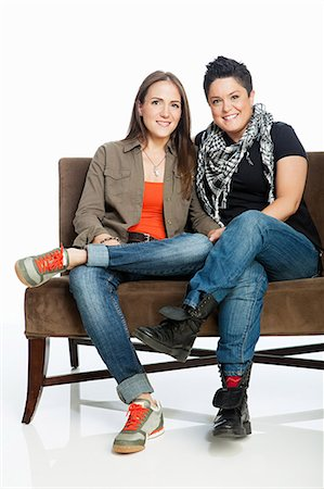 Lesbian couple on sofa against white background Stock Photo - Premium Royalty-Free, Code: 614-05523008