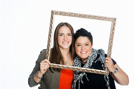 Lesbian couple holding picture frame against white background Stock Photo - Premium Royalty-Free, Code: 614-05523010