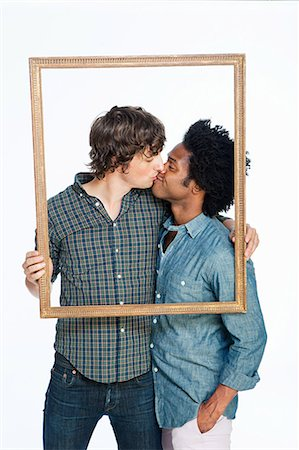Gay couple kissing with picture frame against white background Stock Photo - Premium Royalty-Free, Code: 614-05523028