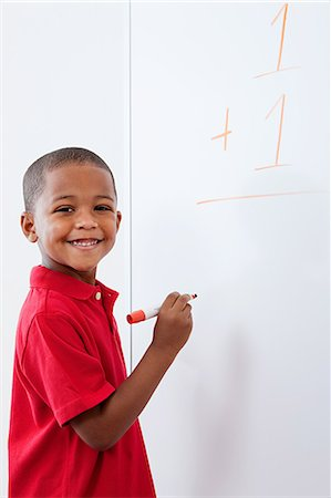 Boy with sum on whiteboard Stock Photo - Premium Royalty-Free, Code: 614-05523126