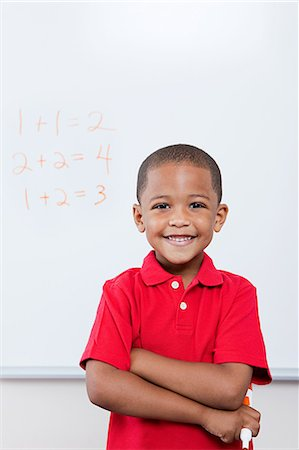Happy schoolboy in front of mathematics on whiteboard Stock Photo - Premium Royalty-Free, Code: 614-05523128