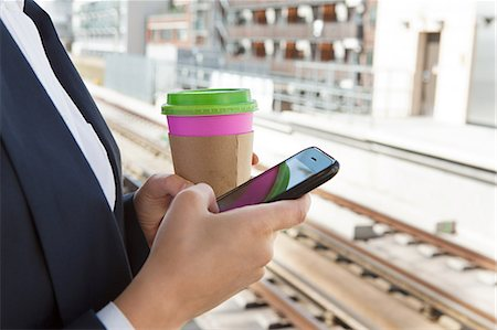 platform - Close up of woman with coffee and smart phone in train station Stock Photo - Premium Royalty-Free, Code: 614-05556688