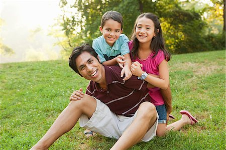 filipino - Father sitting with children in park, portrait Stock Photo - Premium Royalty-Free, Code: 614-05556852