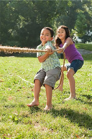 filipino ethnicity - Brother and sister playing tug of war in park Stock Photo - Premium Royalty-Free, Code: 614-05556867