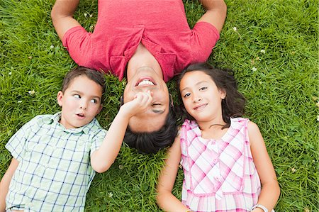 filipino - Father lying on grass with son and daughter Stock Photo - Premium Royalty-Free, Code: 614-05556861