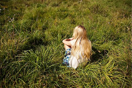 Young woman sitting peacefully in a field Stock Photo - Premium Royalty-Free, Code: 614-05557077