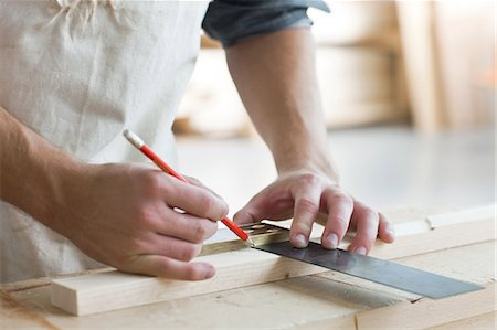 Carpenter using mitre in workshop Stock Photo - Premium Royalty-Free, Code: 614-05557234