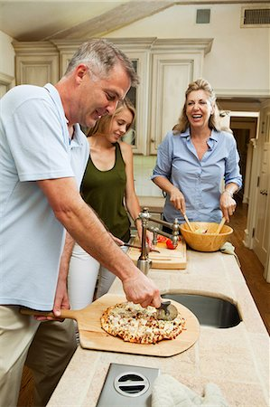 Family preparing pizza together in kitchen Stock Photo - Premium Royalty-Free, Code: 614-05557374