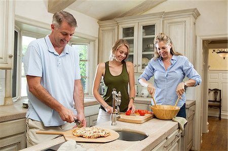 Family preparing pizza together in kitchen Stock Photo - Premium Royalty-Free, Code: 614-05557373
