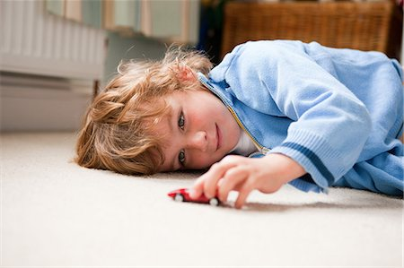 Young boy lying on his side playing with a toy car Stock Photo - Premium Royalty-Free, Code: 614-05650617
