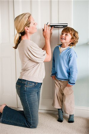 dece11 - Mother measuring her son against a door with a book Stock Photo - Premium Royalty-Free, Code: 614-05650619