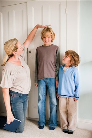 dominant woman - Mother measuring her sons at home Stock Photo - Premium Royalty-Free, Code: 614-05650620