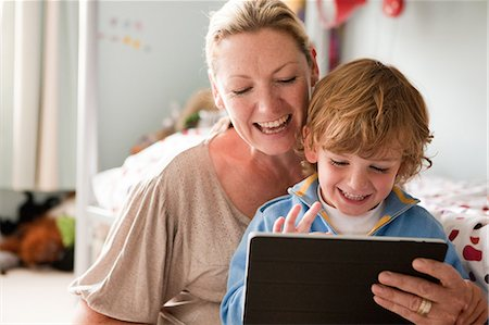 Mother using a digital tablet with her son Stock Photo - Premium Royalty-Free, Code: 614-05650621