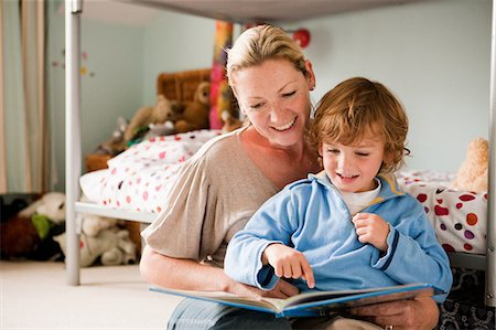 Mother reading a book with her son in his bedroom Stock Photo - Premium Royalty-Free, Code: 614-05650622