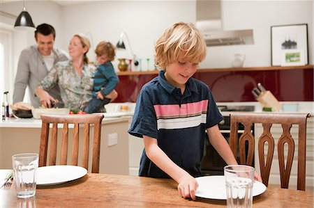 Son helping to lay table with parents and brother visible behind in kitchen Stock Photo - Premium Royalty-Free, Code: 614-05650637