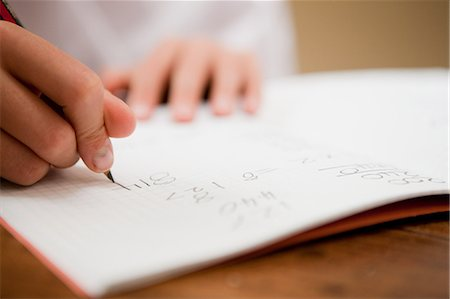 Close up of the hands of a young boy writing in a textbook Stock Photo - Premium Royalty-Free, Code: 614-05650646