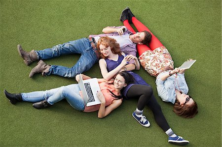 Four people lying down with a laptop, digital tablet and mobile phone Stock Photo - Premium Royalty-Free, Code: 614-05650686