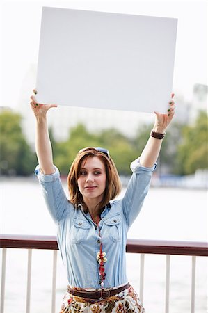 Young woman holding up a white board Stock Photo - Premium Royalty-Free, Code: 614-05650690