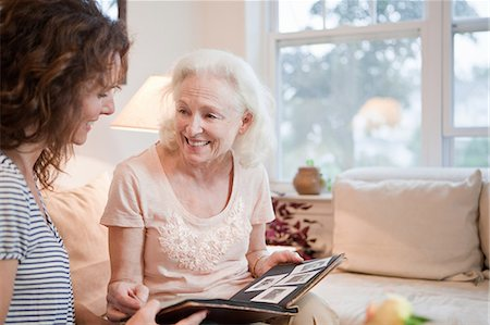 Senior woman and daughter looking through photo album Stock Photo - Premium Royalty-Free, Code: 614-05650754