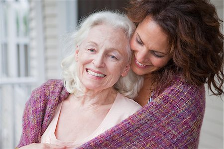 Senior woman and daughter embracing on porch, portrait Stock Photo - Premium Royalty-Free, Code: 614-05650760