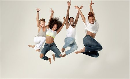 Four young adults jumping in the air with joy Stock Photo - Premium Royalty-Free, Code: 614-05650916