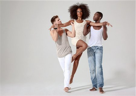 dominant woman - Two men holding a young woman off the ground Stock Photo - Premium Royalty-Free, Code: 614-05650917